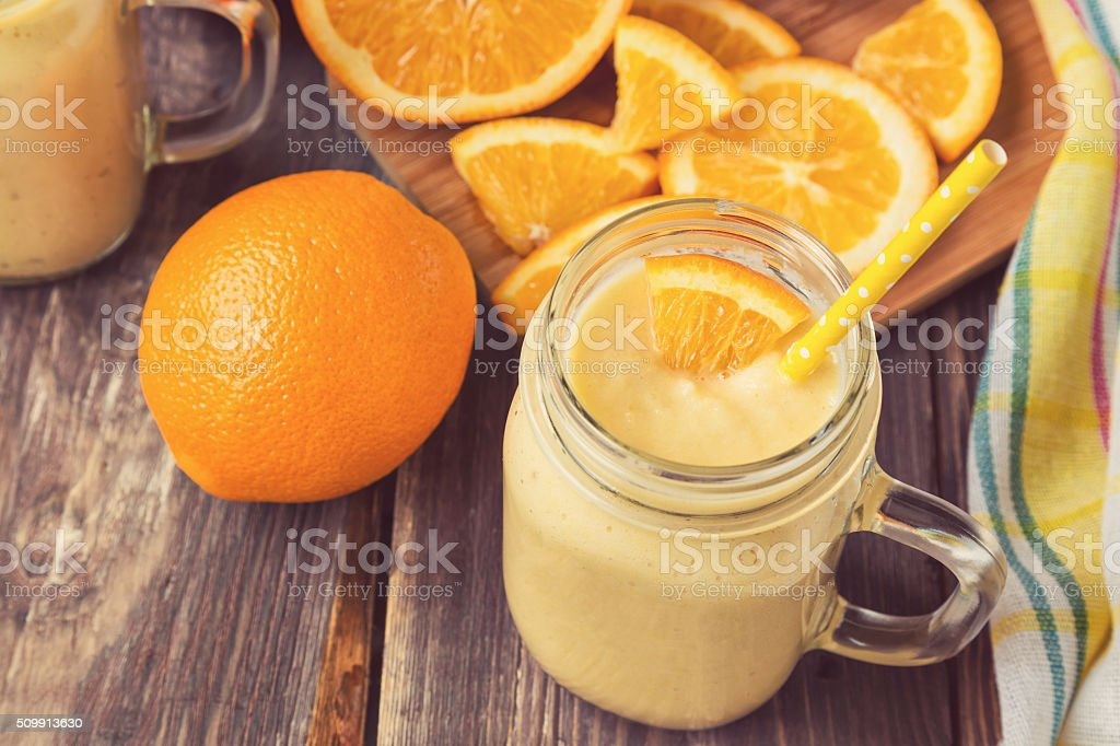 Orange fruit smoothie in the glass jar stock photo