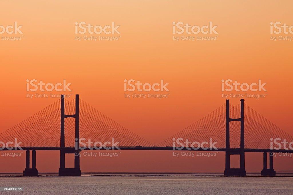 Orange glow at sunset behind the Severn road bridge UK stock photo