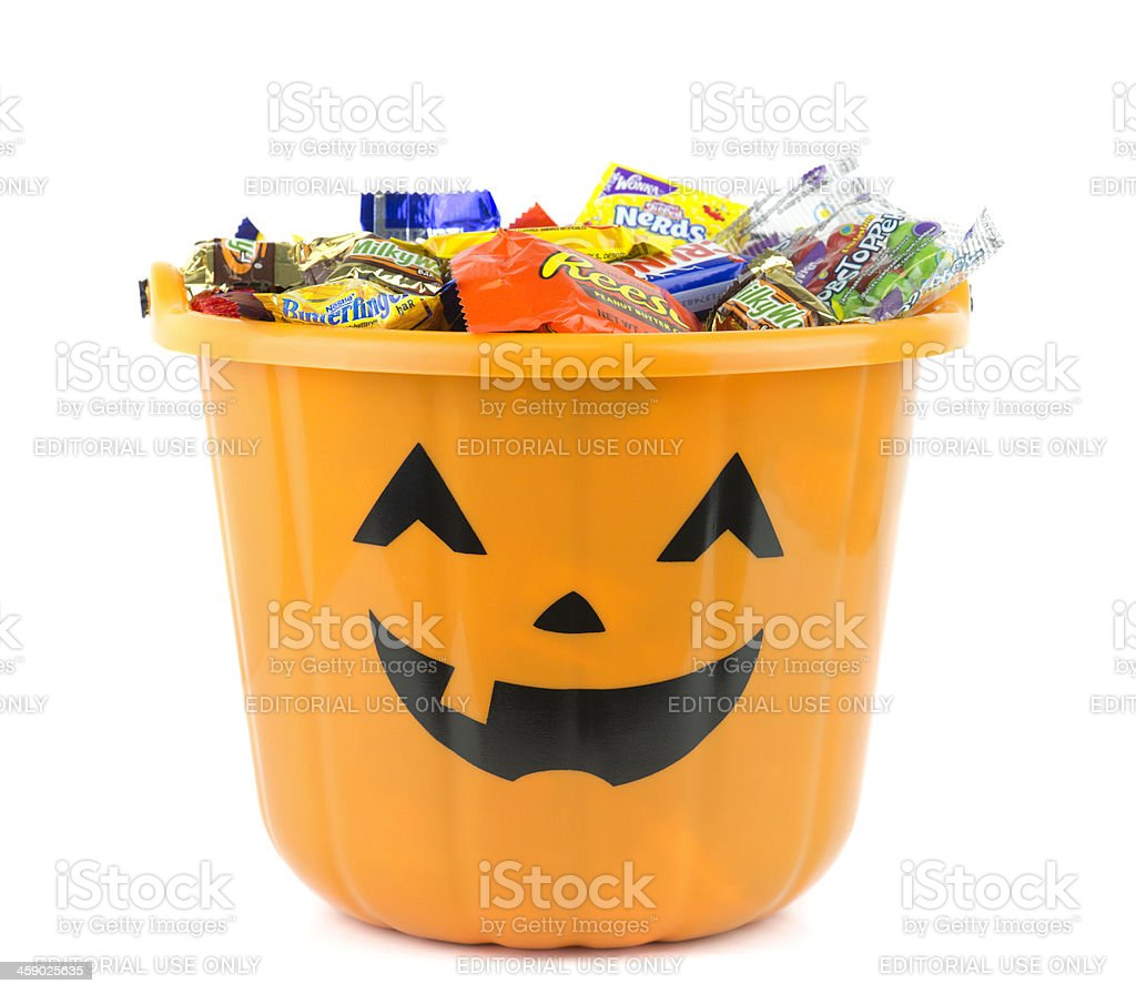 Orange Halloween bucket filled with candy stock photo