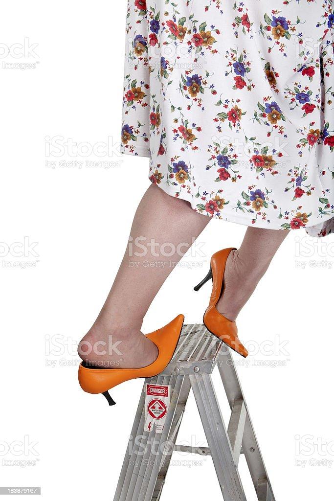 orange heeled woman slips off ladder stock photo