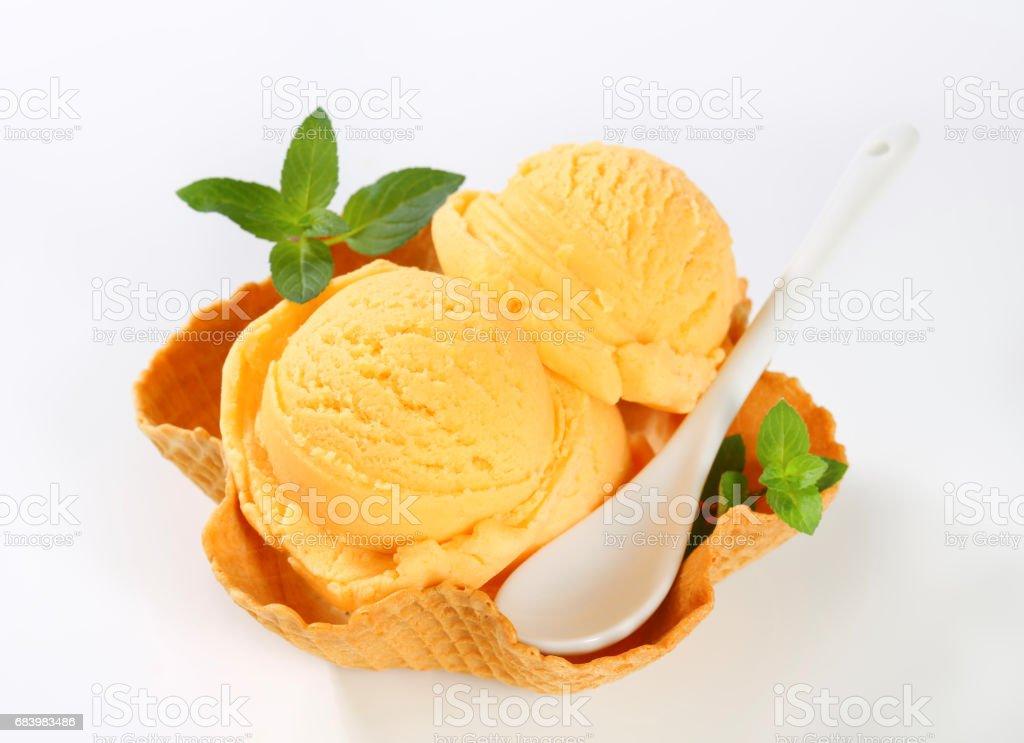 orange ice cream in a waffle basket stock photo