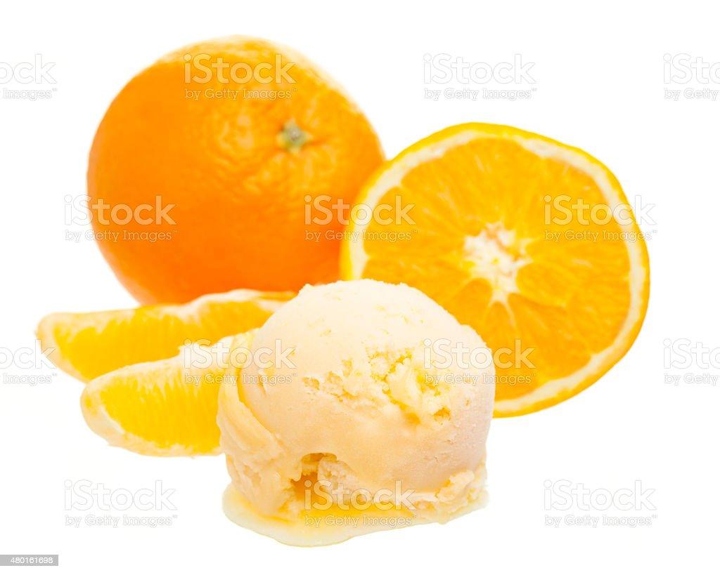 orange ice cream scoop in front of whole orange stock photo
