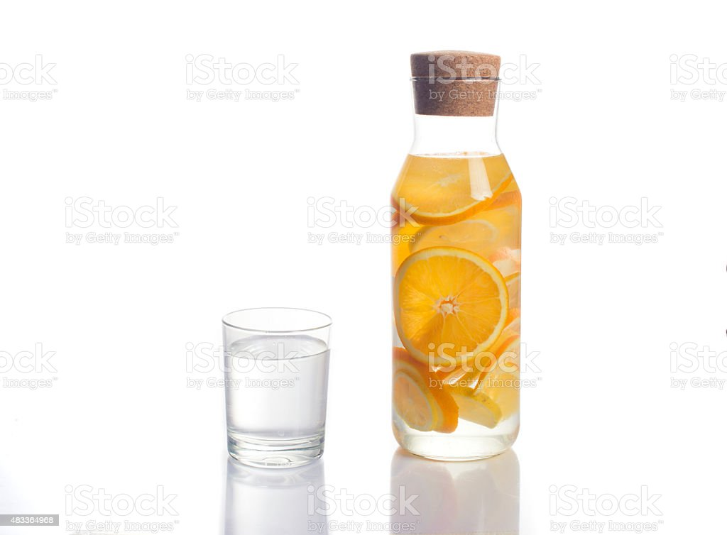 orange infused water in a carafe on white background stock photo