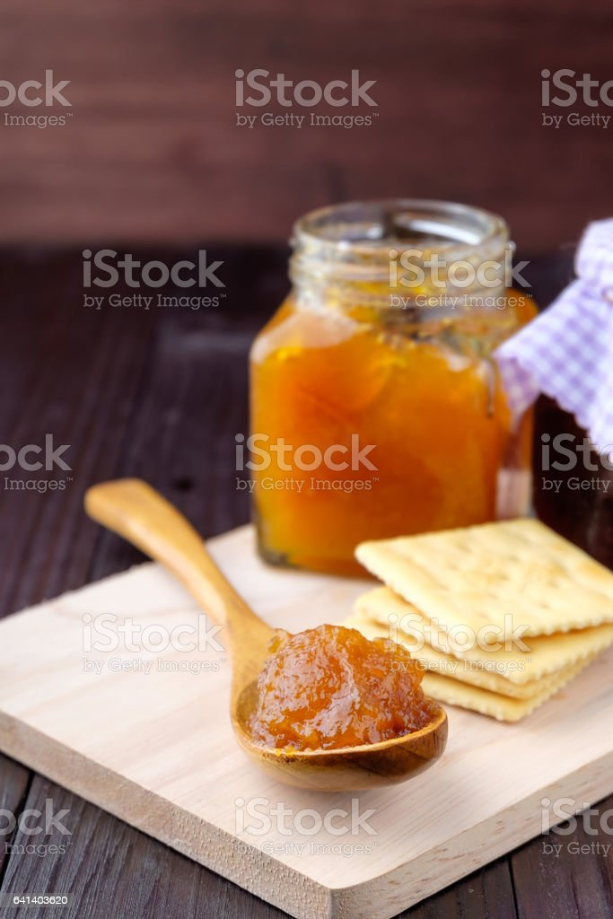 Orange jam on wooden background stock photo