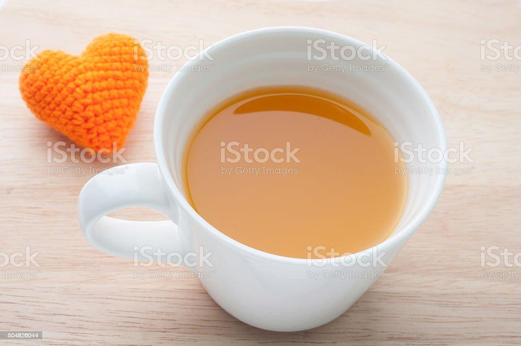 Orange juice and knitted fabrics heart shape on wooden backgroun stock photo