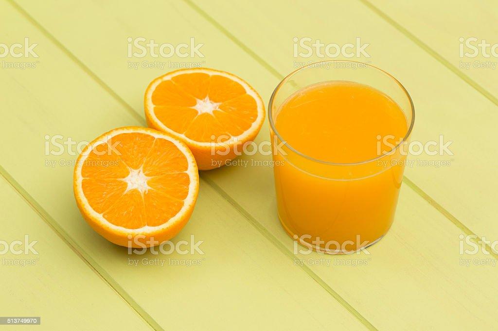 Orange juice and slices of orange on green table stock photo