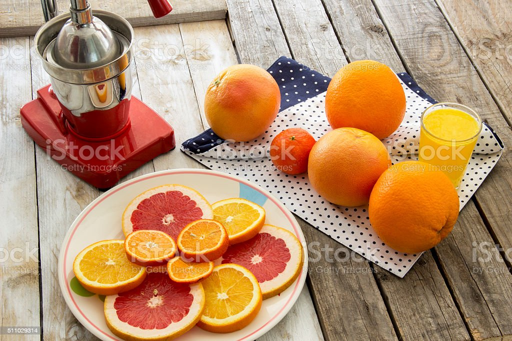 Orange juice, citrus slices and press juicer on wooden table stock photo