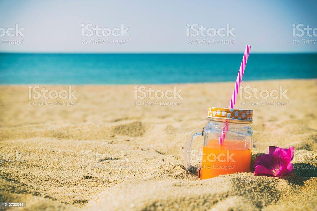 Orange juice in jar on the beach. stock photo
