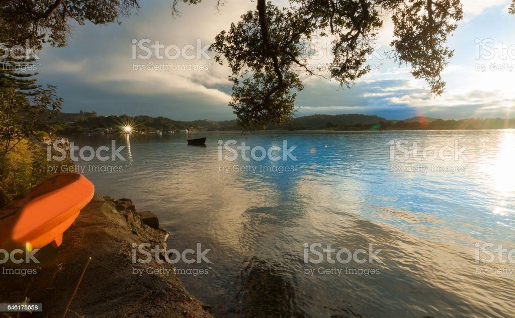 Orange kayak on waters edge estuary at sunrise stock photo