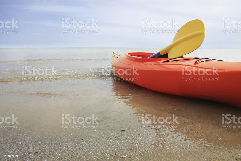 Orange kayak with yellow paddle anchored in the beach royalty-free stock photo