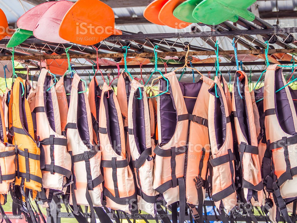 Orange life jackets and colorful paddles for services stock photo