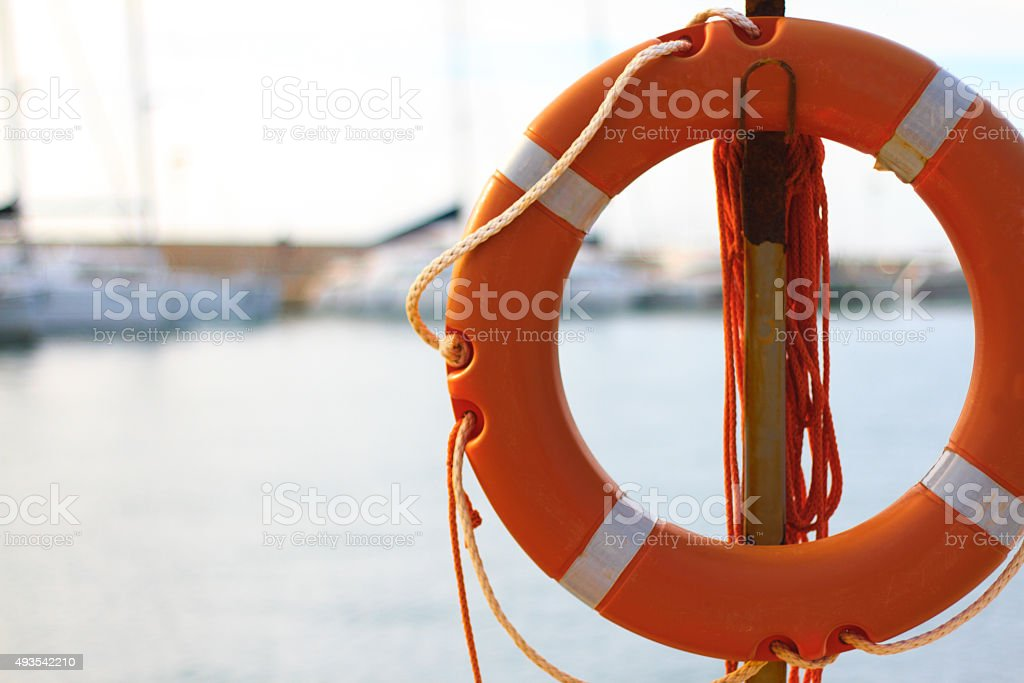 Orange Life Preserver-Ring; Sea and Sailboats in Blurred Background stock photo