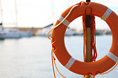 Orange Life Preserver-Ring; Sea and Sailboats in Blurred Background