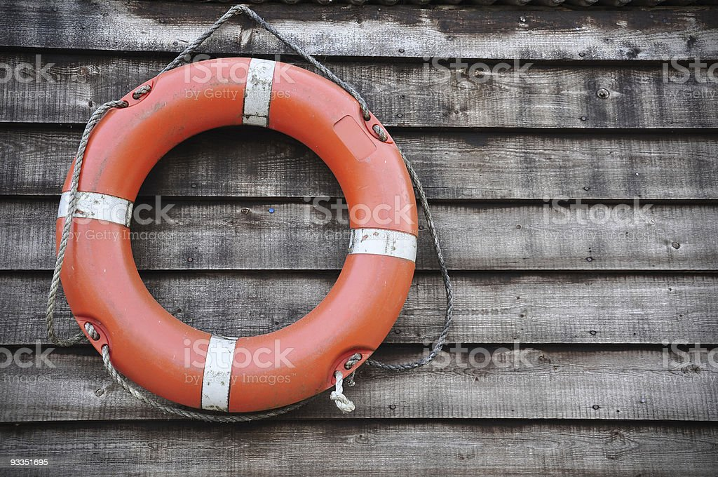 Orange Lifebuoy hanging on wood wall stock photo