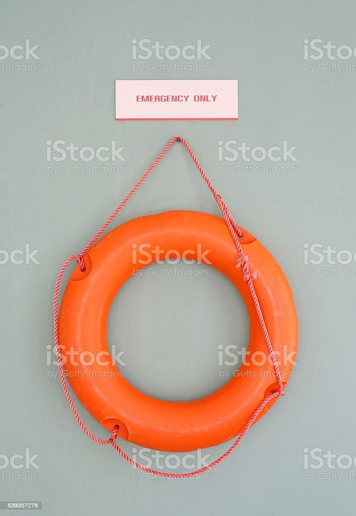 Orange Lifebuoy on a Gray Wall Background stock photo