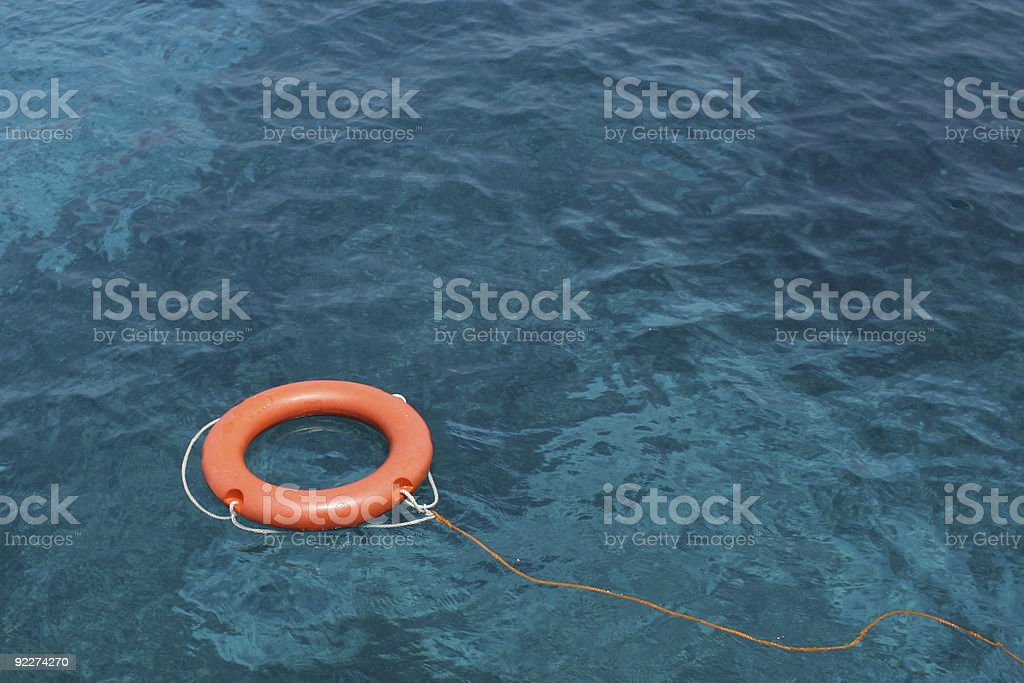 Orange Lifesaving ring floating on clear blue sea stock photo