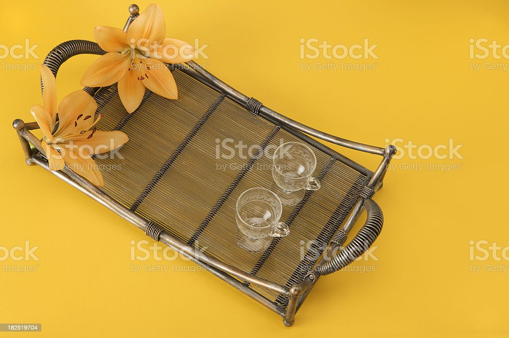 Orange lilies and two glasses on an ornamental tray. royalty-free stock photo