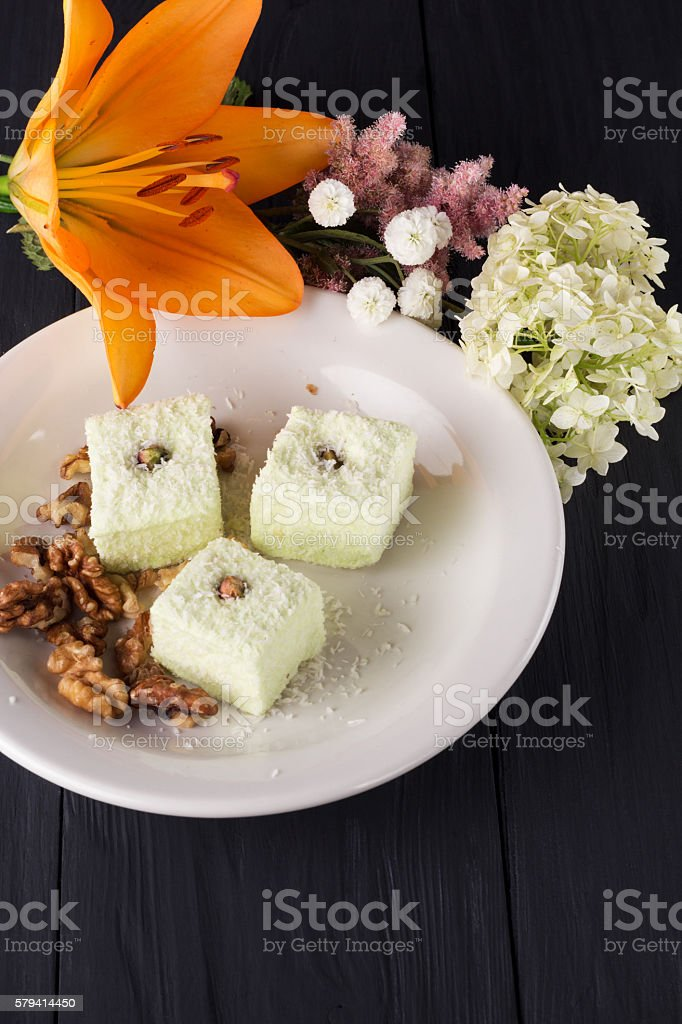 orange lily and candies on plate stock photo