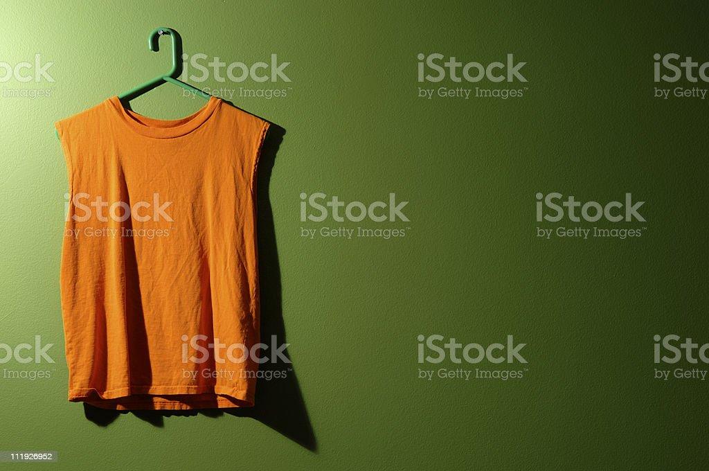 Orange Men's Tank top on Green Wall royalty-free stock photo