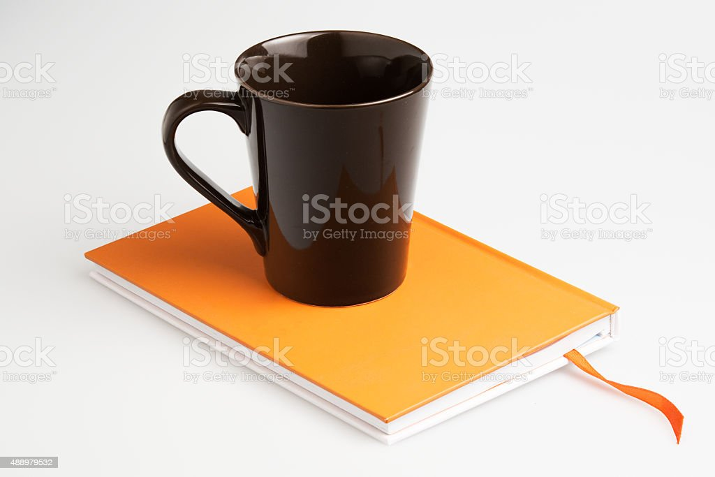 Orange note book white pen and cup stock photo