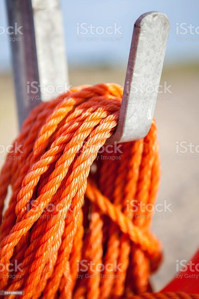 Orange nylon safety rope coiled on metal hook stock photo