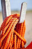 Orange nylon safety rope coiled on metal hook