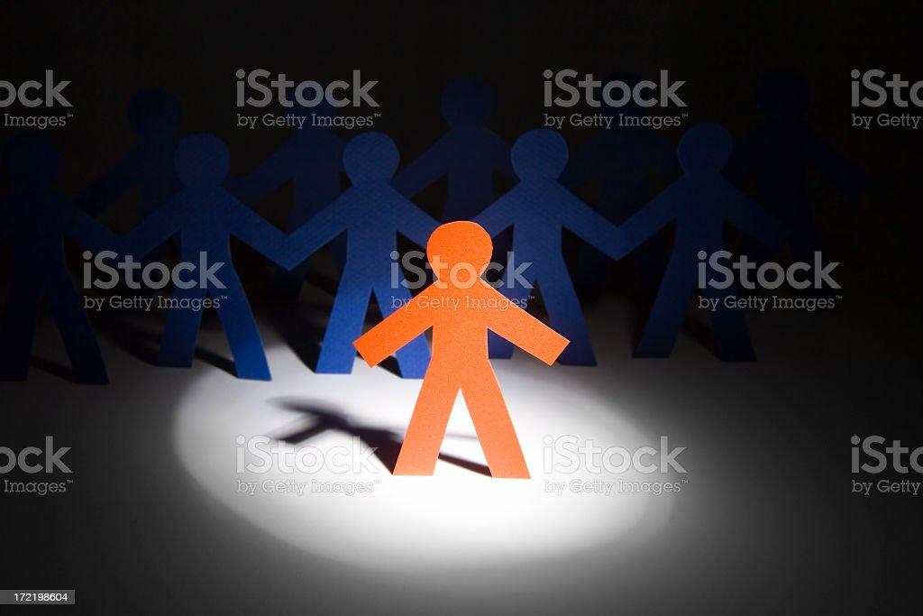 Orange paper doll under a spotlight stock photo