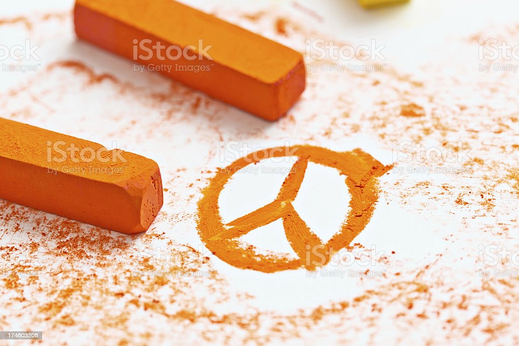 Orange pastel sketch of Peace sign on drawing pad stock photo