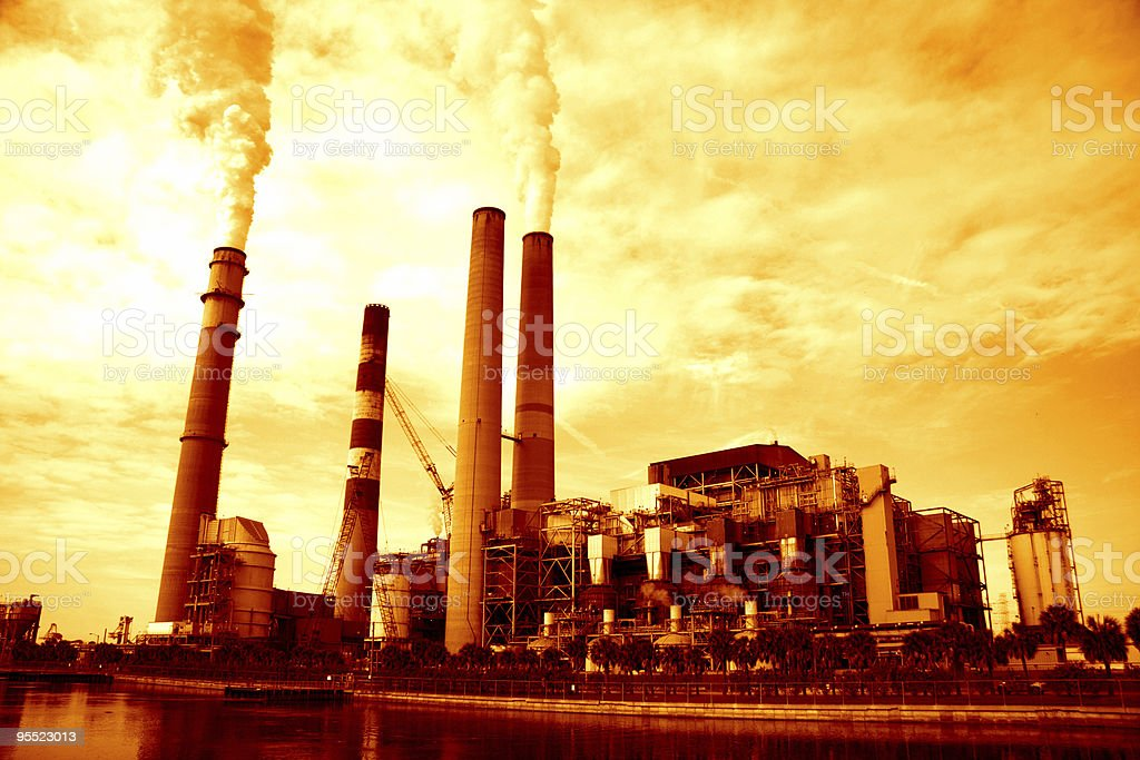 Orange photo of an industrial plant producing smoke royalty-free stock photo