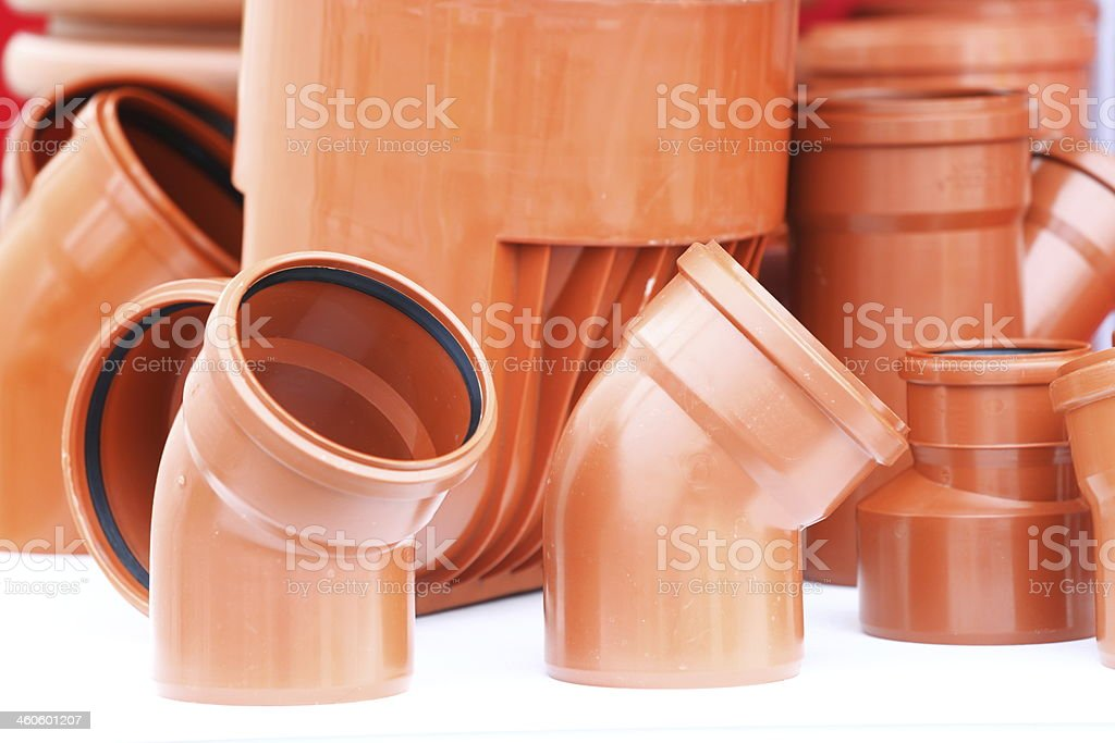 orange pieces- drain pipes pvc on white background stock photo