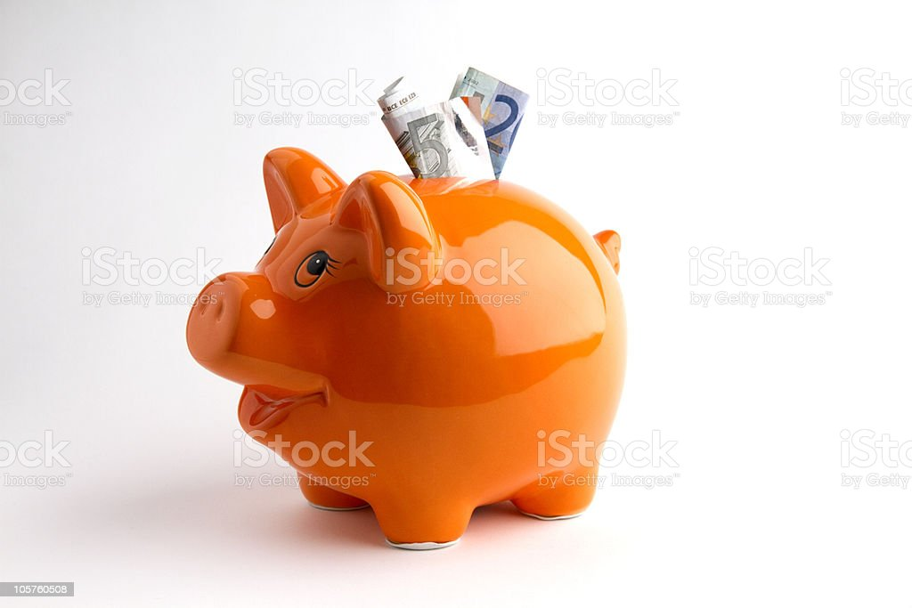 Orange piggy bank with bills coming out of the top stock photo