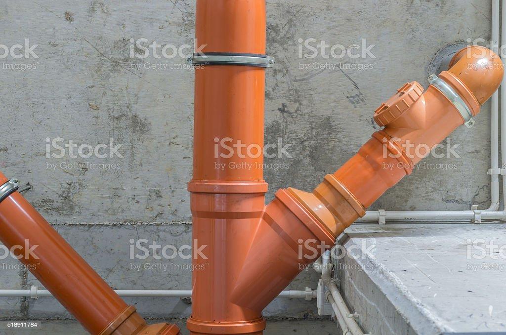 orange plastic pipe, tee, elbow, fitting, valve, sanitary sewer system stock photo