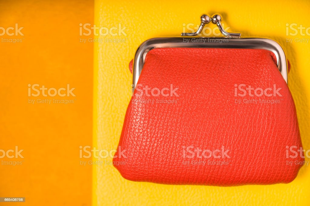 Orange purse on the bright yellow background top view stock photo