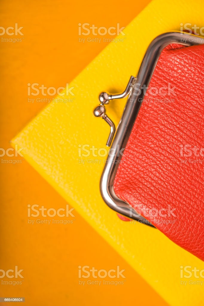 Orange purse on the bright yellow background vertical stock photo