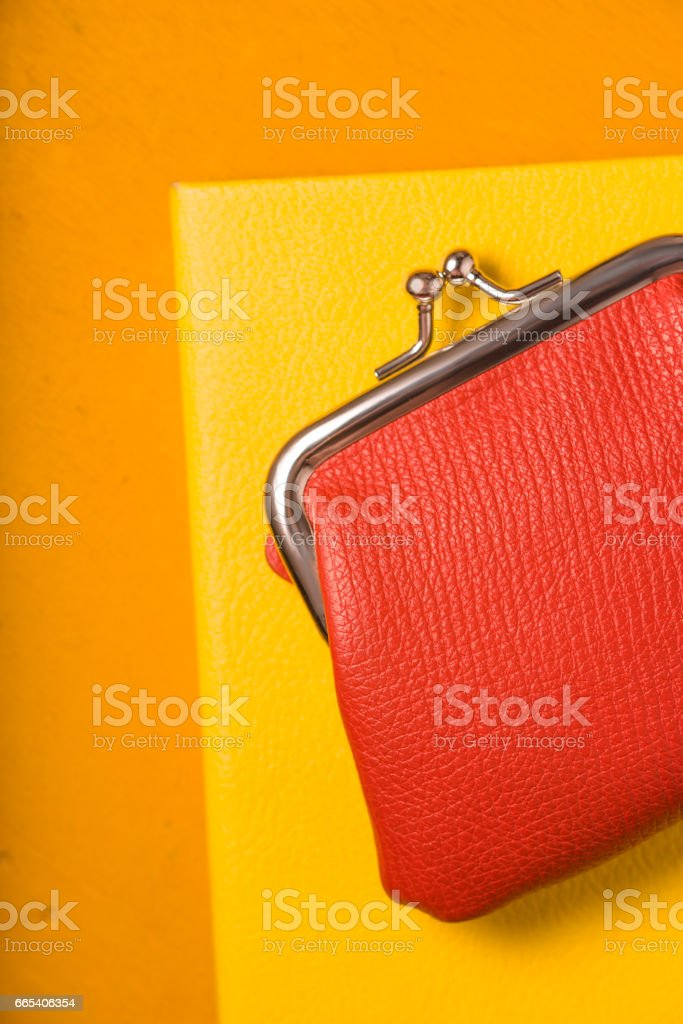 Orange purse  with notebook on the bright yellow background vertical stock photo