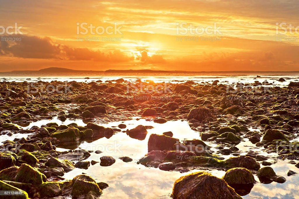 orange reflections at rocky beal beach stock photo