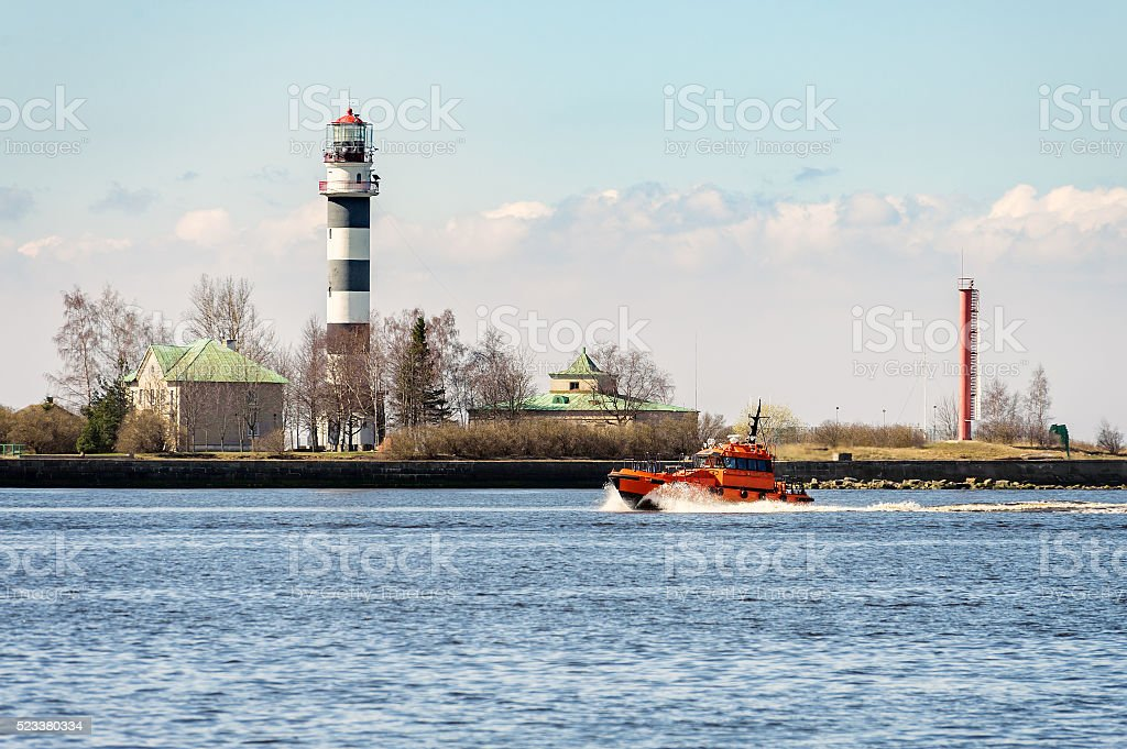 Orange rescue tug entering port of Riga town in Latvia stock photo