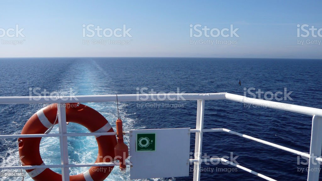 Orange ring life boy on white ferryboat.Obligatory ship safety equipment.Personal flotation device.Lifesaver on the deck of a ferry vessel.Prevent drowning.Boat travel to Asinara island,Sardinia,Italy.Lifebuoy with light. Shipping in the mediterranean. stock photo