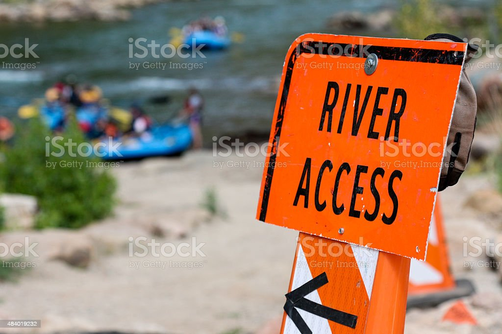 Orange River Access sign with blurry rafts behind stock photo