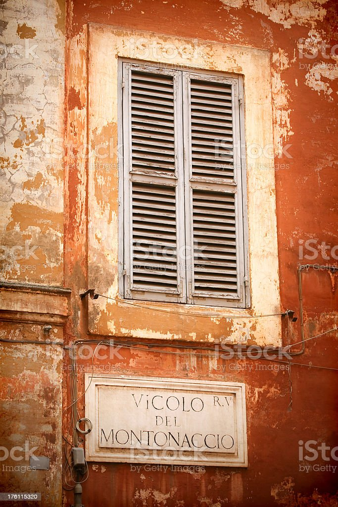 Orange Roman grunge wall with street name sign and shutters royalty-free stock photo