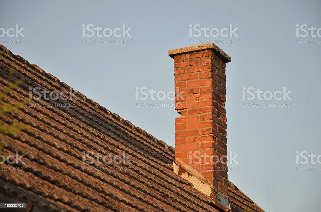 Orange roof tiles, brick chimney and blue sky stock photo