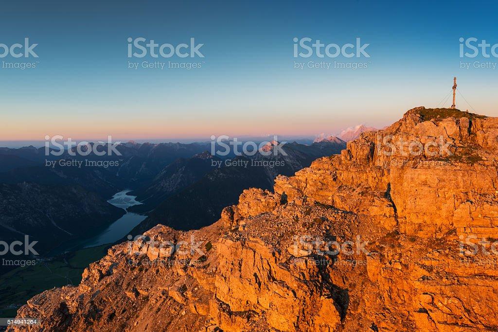 orange rough rocks of mountain at sunset light at fall stock photo