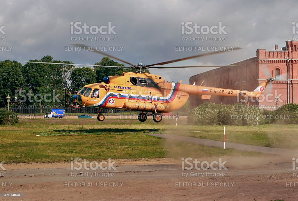 Orange russian Mi-8 helicopter is landing on grass lawn. royalty-free stock photo