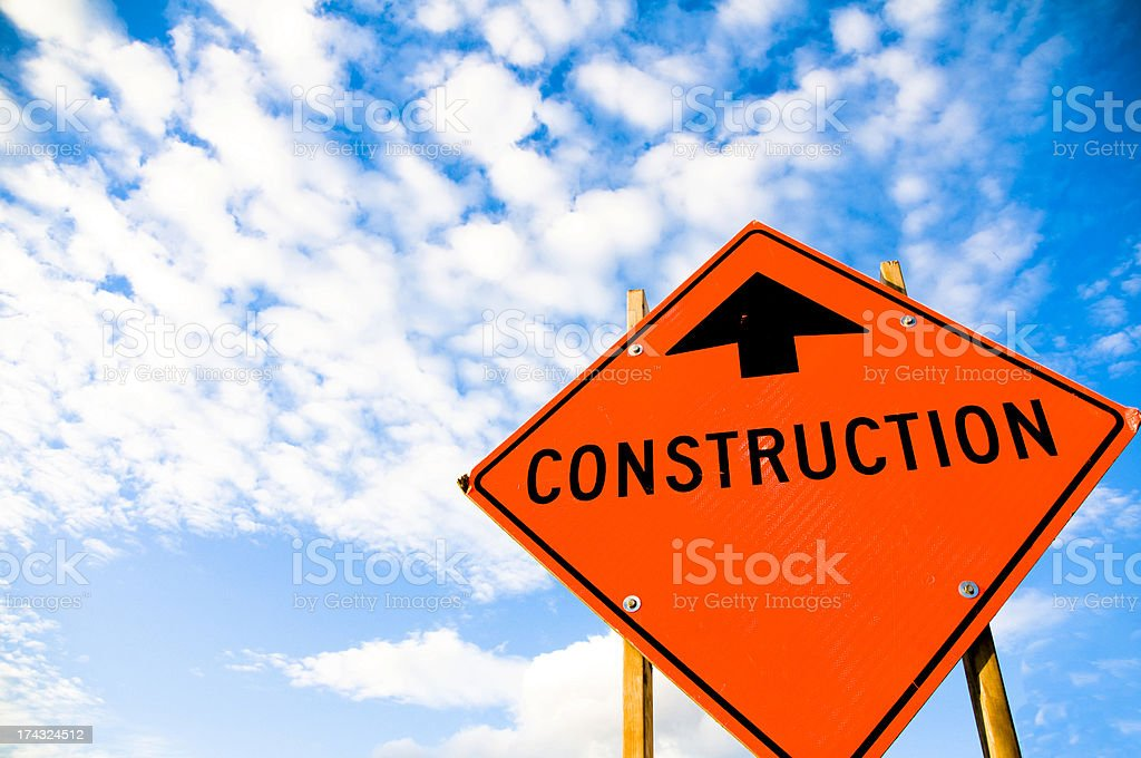Orange sign with arrow and construction word with blue sky stock photo