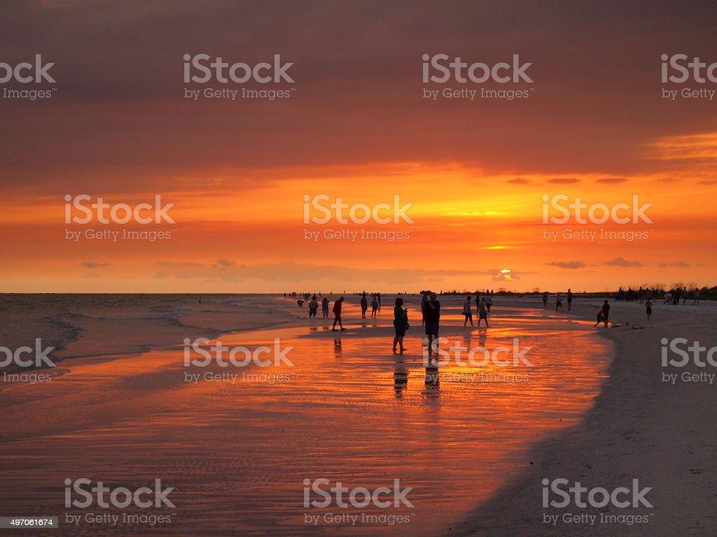 Orange sky at sunset on coastal beach stock photo