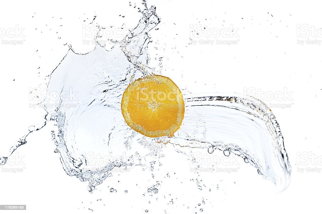 Orange slice falling and splashing into clear water. royalty-free stock photo