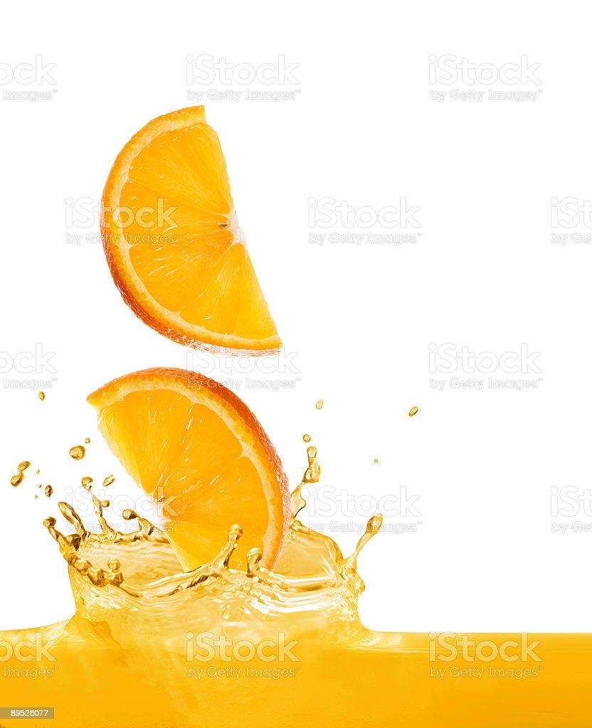 Orange slices splashing into orange juice royalty-free stock photo