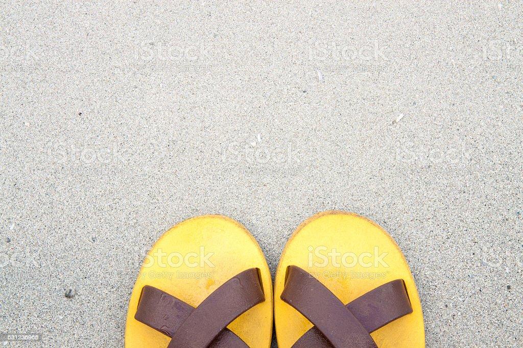Orange slipper on sand background at seaside royalty-free stock photo