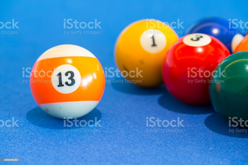 orange snooker ball with number thirteen on table pool stock photo