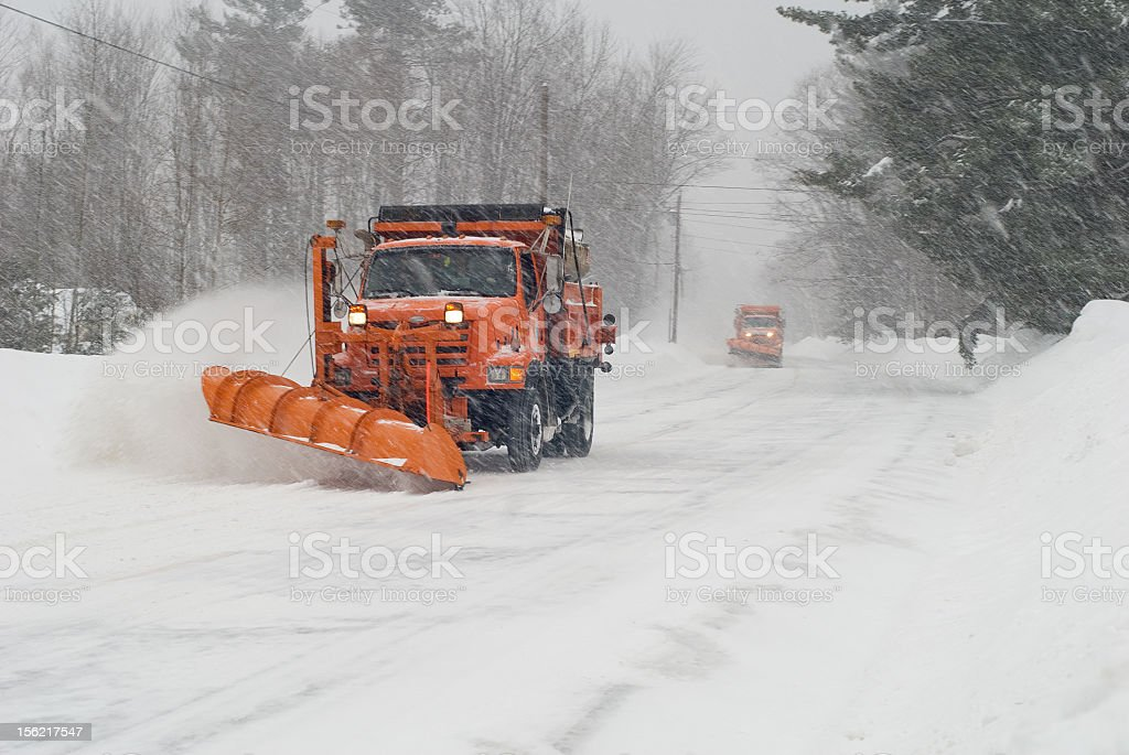 Orange snow plow plowing snow on an empty street stock photo